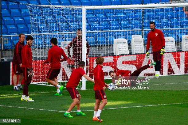 Goalkeeper Jan Oblak stops the ball behind his teamates Antoine Griezmann and Koke during a training session ahead of the UEFA Champions League...