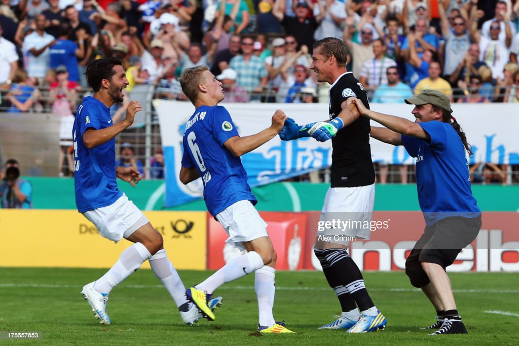 Goalkeeper Jan Zimmermann of Darmstadt celebrates with team mates after Branimir Hrgota of Moenchengladbach missed the final penalty during the penalty shoot-out of the DFB Cup first round match between Darmstadt 98 and Borussia Moenchengladbach at Boellenfalltorstadion on August 4, 2013 in Darmstadt, Germany.