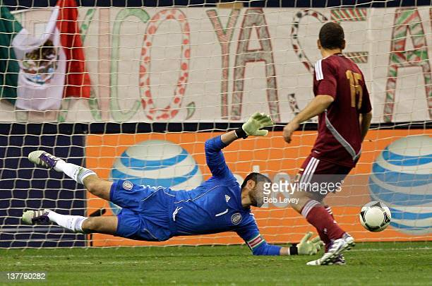 Goalkeeper Jesus Corona of Mexico dives as a shot passes just wide of the net as Alejandro Moreno of Venezuela looks on during the international...