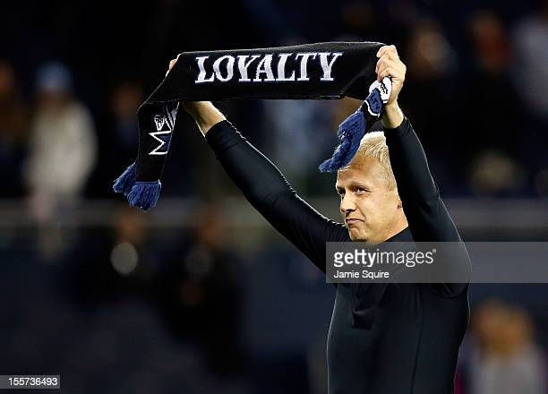 Goalkeeper Jimmy Nielsen of Sporting KC hoists a scarf and applauds fans after the Eastern Conference Semifinal game against the Houston Dynamo at...