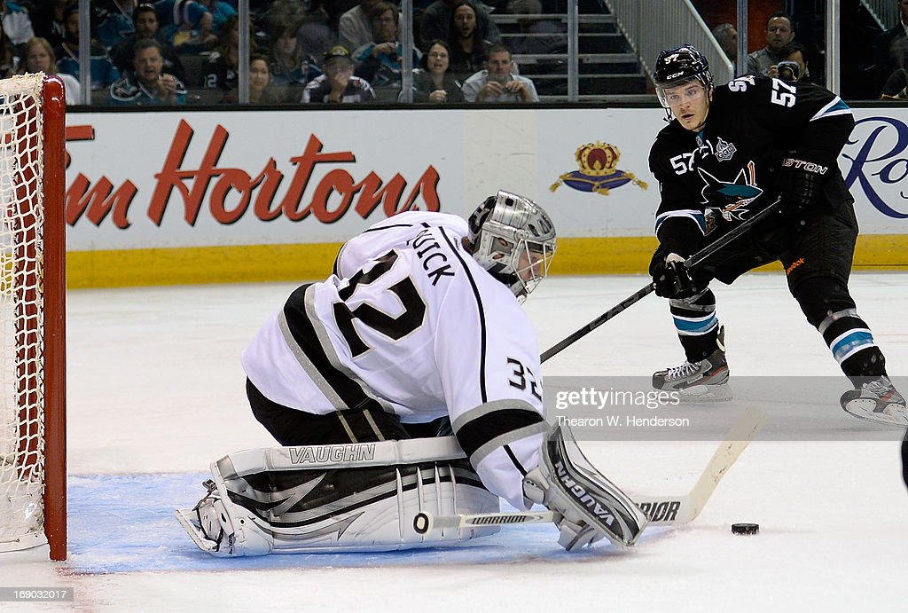 Goalkeeper Jonathan Quick #32 blocks a shot, defending the net against Tommy Wingels #57 of the San Jose Sharks in the second period in Game Three of the Western Conference Semifinals during the 2013 NHL Stanley Cup Playoffs at HP Pavilion on May 18, 2013 in San Jose, California. The Sharks defeated the Kings in overtime 2-1.