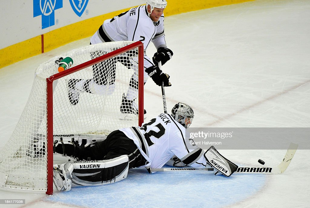Goalkeeper <a gi-track='captionPersonalityLinkClicked' href=/galleries/search?phrase=Jonathan+Quick&family=editorial&specificpeople=2271852 ng-click='$event.stopPropagation()'>Jonathan Quick</a> #32 of the Los Angeles Kings dives to knock away an errant puck during play against the Carolina Hurricanes at PNC Arena on October 11, 2013 in Raleigh, North Carolina.