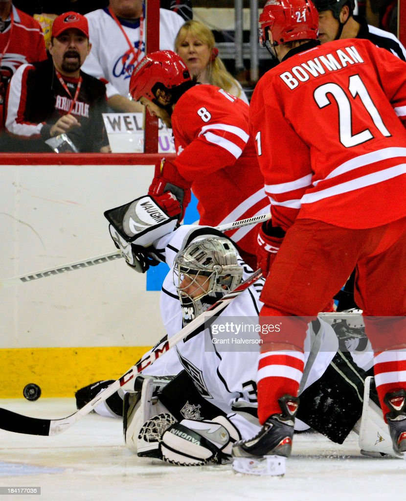 Goalkeeper <a gi-track='captionPersonalityLinkClicked' href=/galleries/search?phrase=Jonathan+Quick&family=editorial&specificpeople=2271852 ng-click='$event.stopPropagation()'>Jonathan Quick</a> #32 of the Los Angeles Kings knocks the puck away, pressured by <a gi-track='captionPersonalityLinkClicked' href=/galleries/search?phrase=Kevin+Westgarth&family=editorial&specificpeople=4537296 ng-click='$event.stopPropagation()'>Kevin Westgarth</a> #8 and <a gi-track='captionPersonalityLinkClicked' href=/galleries/search?phrase=Drayson+Bowman&family=editorial&specificpeople=4111563 ng-click='$event.stopPropagation()'>Drayson Bowman</a> #21 of the Carolina Hurricanes during play at PNC Arena on October 11, 2013 in Raleigh, North Carolina.