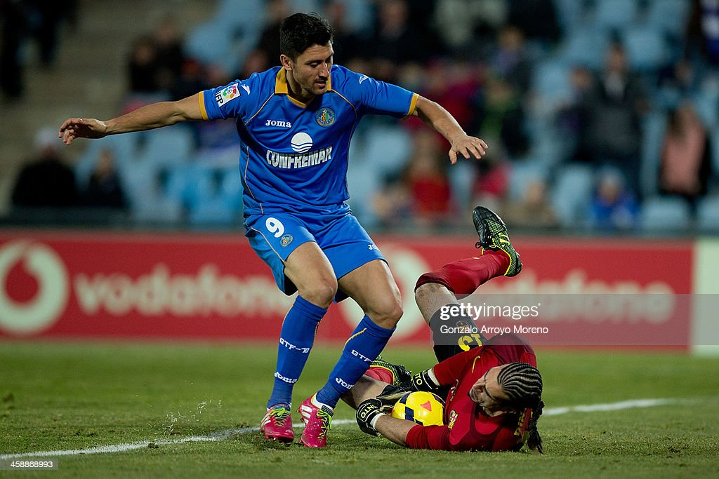 Goalkeeper Jose Manuel Pinto (R) of FC Barcelona stops the ball at the feet of <a gi-track='captionPersonalityLinkClicked' href=/galleries/search?phrase=Ciprian+Marica&family=editorial&specificpeople=2178476 ng-click='$event.stopPropagation()'>Ciprian Marica</a> (L) of Getafe CF during the La Liga match between Getafe CF and FC Barcelona at Coliseum Alfonso Perez on December 22, 2013 in Getafe, Spain.