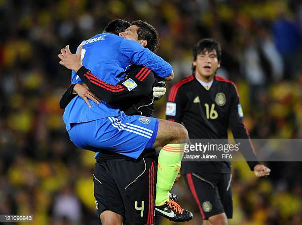 Goalkeeper Jose Rodriguez of Mexico celebrates with Nestor Araujo as Jorge Valencia looks on in the background after their team scored the third goal...