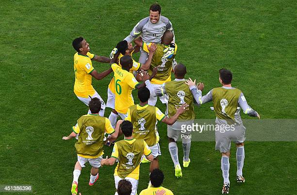 Goalkeeper Julio Cesar of Brazil celebrates with teammates after defeating Chile in a penalty shootout during the 2014 FIFA World Cup Brazil round of...