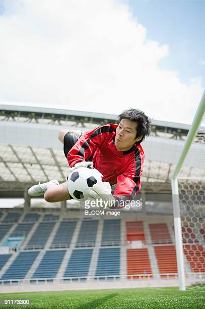 Goalkeeper jumping for ball
