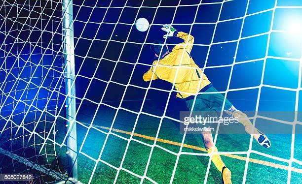 Portiere salti e cerca di bloccare un pallone da calcio