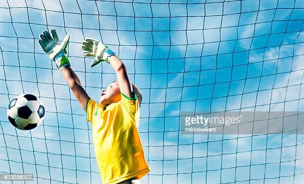 Goalkeeper jumps to block soccer ball from scoring goal