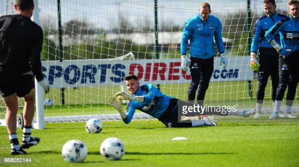 Goalkeeper Karl Darlow makes a dive to save the ball during the Newcastle United Training Session at The Newcastle United Training Centre on April 13...