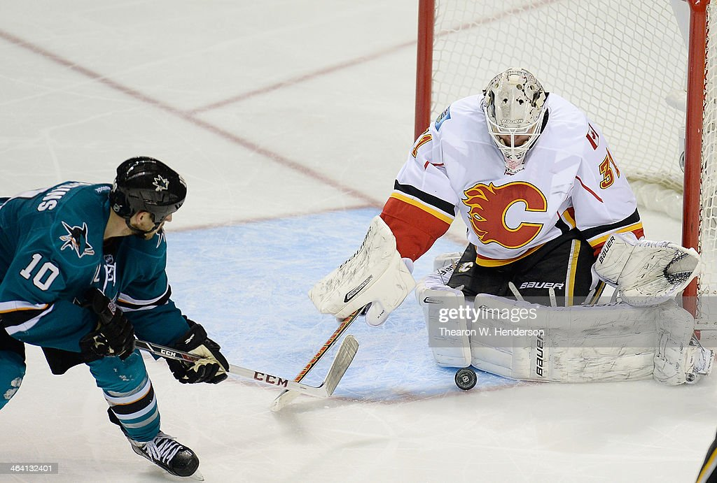 Goalkeeper <a gi-track='captionPersonalityLinkClicked' href=/galleries/search?phrase=Karri+Ramo&family=editorial&specificpeople=716721 ng-click='$event.stopPropagation()'>Karri Ramo</a> #31 of the Calgary Flames blocks the shot of <a gi-track='captionPersonalityLinkClicked' href=/galleries/search?phrase=Andrew+Desjardins&family=editorial&specificpeople=2748431 ng-click='$event.stopPropagation()'>Andrew Desjardins</a> #10 of the San Jose Sharks during the third period at SAP Center on January 20, 2014 in San Jose, California. The Sharks won the game 3-2.