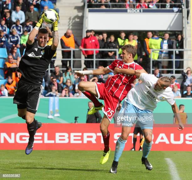 Goalkeeper Kevin Kunz of chemnitz and Thomas Mueller of Bayern Muenchen and Maurice Trapp of Chemnitz battle for the ball during the DFB Cup first...