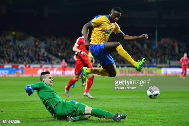 Goalkeeper Kevin Mueller of Heidenheim clears the ball ahead of Suleiman Abdullahi of Braunschweig during the Second Bundesliga match between...
