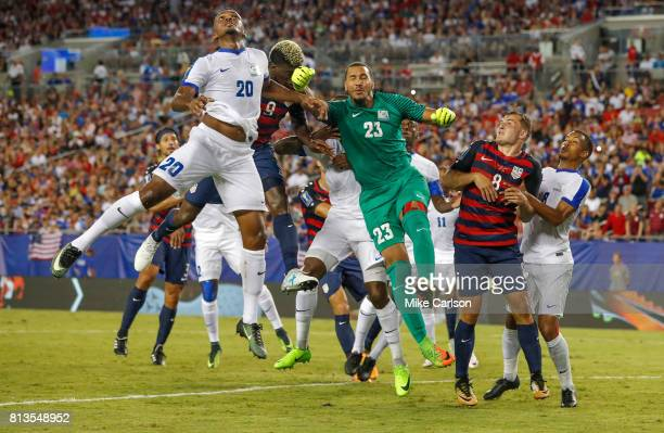 Goalkeeper Kevin Olimpa of Martinique knocks the ball away from Gyasi Zardes of the United States as Stephane Abaul of Martinique defends during the...