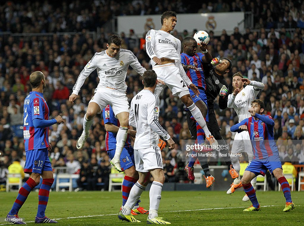 Goalkeeper Keylor Navas of Levante makes a save against Raphael Varane and Cristiano Ronaldo of Real Madrid during the La Liga match between Real Madrid and Levante UD at Estadio Santiago Bernabeu on March 9, 2014 in Madrid, Spain.