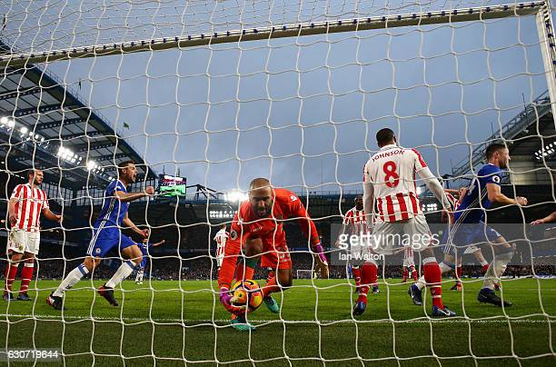 Goalkeeper Lee Grant of Stoke City grabs the ball as Gary Cahill of Chelsea celebrates as he scores the opening goal during the Premier League match...