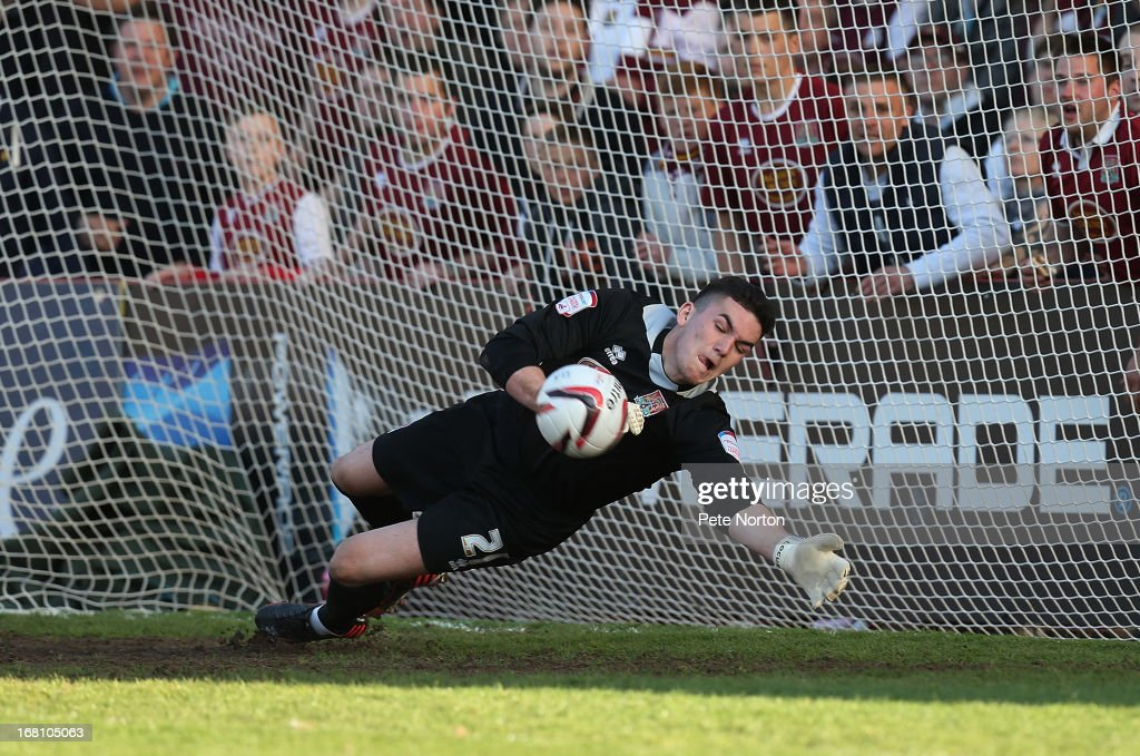 Goalkeeper Lee Nicholls of Northampton Town dives to save a penalty taken by Marlon Pack of Cheltenham Town during the npower League Two Play Off Semi Final Second Leg between Cheltenham Town and Northampton Town at Abbey Business Stadium on May 5, 2013 in Cheltenham, England.