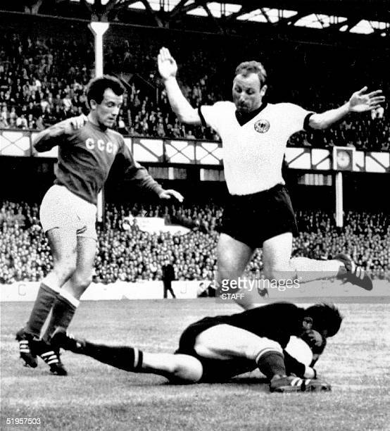 Goalkeeper Lev Yashin from the Soviet Union protects himself after recovering the ball in front of German forward Uwe Seeler 25 July 1966 in...