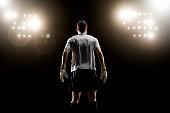 Goalkeeper looking at stadium light, rear view