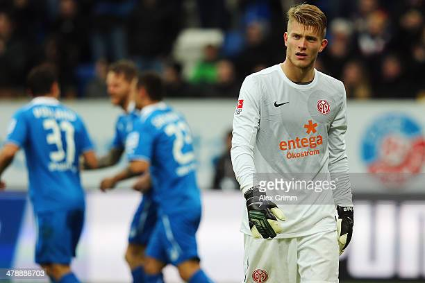 Goalkeeper Lorius Karius of Mainz reacts as Eugen Polanski of Hoffenheim celebrates his team's first goal with team mates during the Bundesliga match...