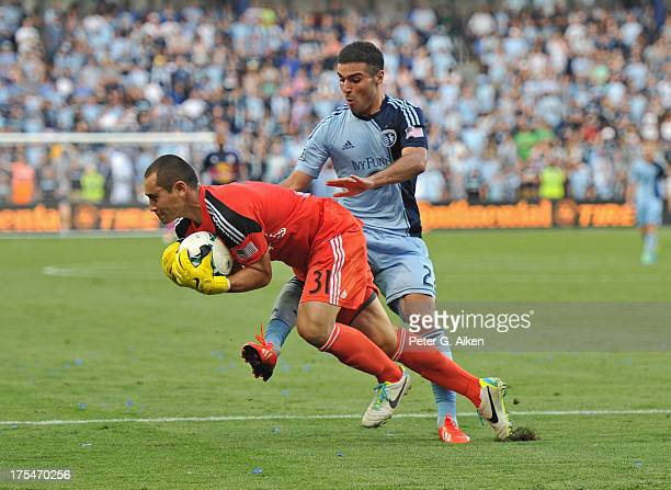 Goalkeeper Luis Robles of the New York Red Bulls makes a save against pressure from forward Soony Saad of Sporting Kansas City during the second half...