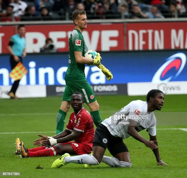 Goalkeeper Lukas Hradecky of Frankfurt and Chadrac Akolo of Stuttgart and Taleb Tawatha of Frankfurt battle for the ball during the Bundesliga match...