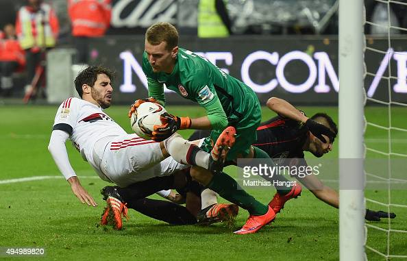 Goalkeeper Lukas Hradecky of Frankfurt saves a ball against Javi Martinez of Muenchen during the Bundesliga match between Eintracht Frankfurt and FC...