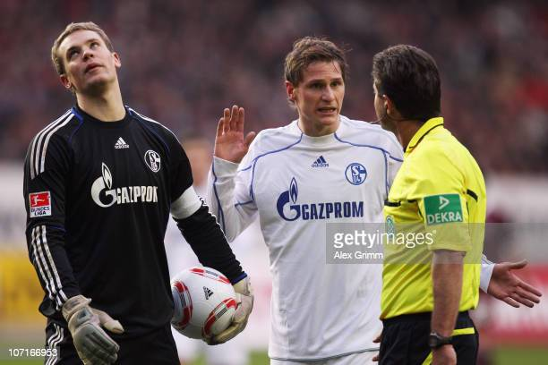 Goalkeeper Manuel Neuer and Benedikt Hoewedes of Schalke discuss with referee Guenter Perl during the Bundesliga match between 1 FC Kaiserslautern...