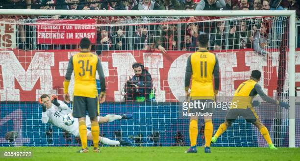Goalkeeper Manuel Neuer of Bayern Munich saves a penalty taken by Alexis Sánchez of Arsenal during the UEFA Champions League Round of 16 first leg...