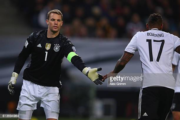 Goalkeeper Manuel Neuer of Germany shakes hands with team mate Jerome Boateng during the FIFA World Cup 2018 qualifying match between Germany and...