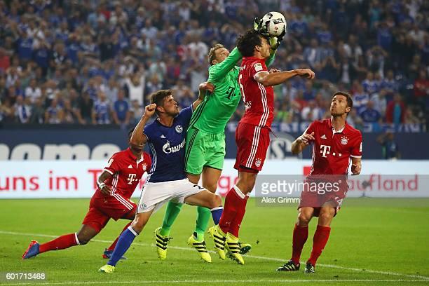 Goalkeeper Manuel Neuer of Muenchen catches the ball ahead of team mate Mats Hummels and KlaasJan Huntelaar of Schalke during the Bundesliga match...