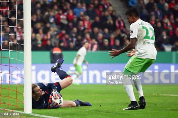 Goalkeeper Manuel Neuer of Muenchen holds the ball next to Luiz Gustavo of Wolfsburg during the DFB Cup Round Of 16 match between Bayern Muenchen and...