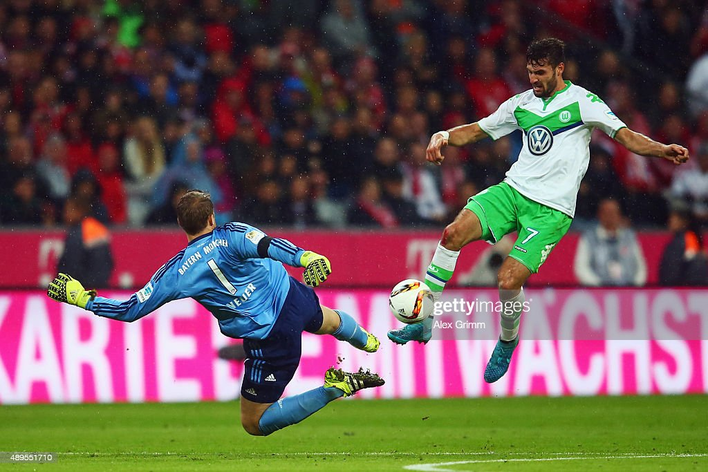 Goalkeeper <a gi-track='captionPersonalityLinkClicked' href=/galleries/search?phrase=Manuel+Neuer&family=editorial&specificpeople=764621 ng-click='$event.stopPropagation()'>Manuel Neuer</a> of Muenchen is challenged by <a gi-track='captionPersonalityLinkClicked' href=/galleries/search?phrase=Daniel+Caligiuri&family=editorial&specificpeople=6495349 ng-click='$event.stopPropagation()'>Daniel Caligiuri</a> of Wolfsburg during the Bundesliga match between FC Bayern Muenchen and VfL Wolfsburg at Allianz Arena on September 22, 2015 in Munich, Germany.