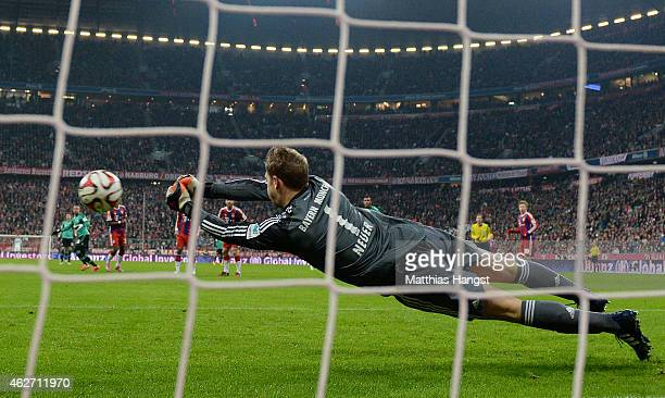 Goalkeeper Manuel Neuer of Muenchen saves a penalty of Eric Maxim ChoupoMoting of Schalke during the Bundesliga match between FC Bayern Muenchen and...