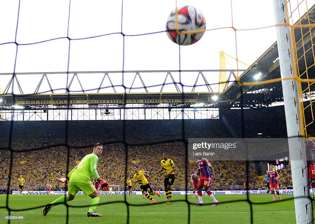 Goalkeeper <a gi-track='captionPersonalityLinkClicked' href=/galleries/search?phrase=Manuel+Neuer&family=editorial&specificpeople=764621 ng-click='$event.stopPropagation()'>Manuel Neuer</a> of Munich looks on as <a gi-track='captionPersonalityLinkClicked' href=/galleries/search?phrase=Henrikh+Mkhitaryan&family=editorial&specificpeople=6234732 ng-click='$event.stopPropagation()'>Henrikh Mkhitaryan</a> #10 of Dortmund scores the opening goal during the DFL Supercup between Borrussia Dortmund and FC Bayern Muenchen at Signal Iduna Park on August 13, 2014 in Dortmund, Germany.