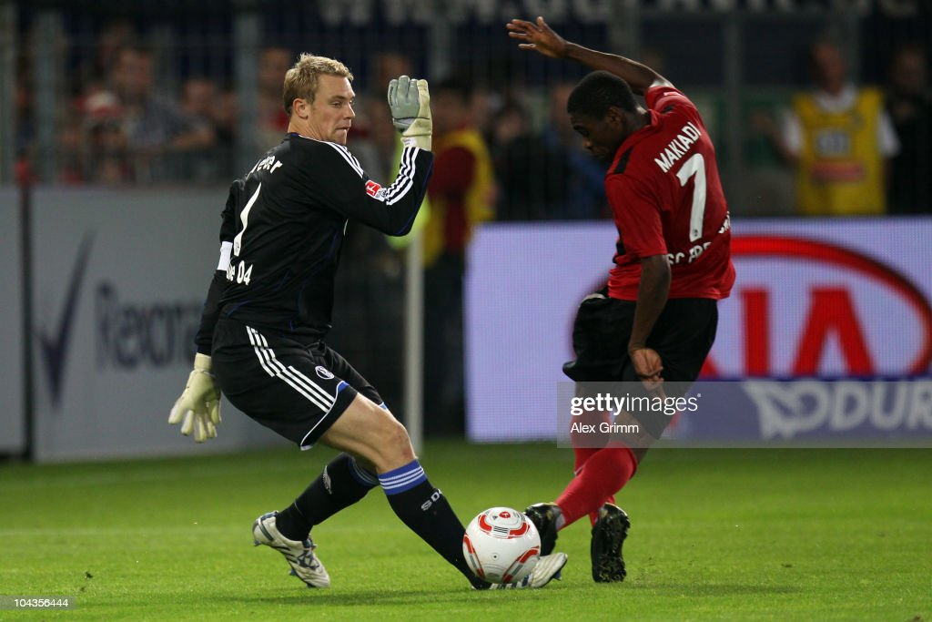 Goalkeeper <a gi-track='captionPersonalityLinkClicked' href=/galleries/search?phrase=Manuel+Neuer&family=editorial&specificpeople=764621 ng-click='$event.stopPropagation()'>Manuel Neuer</a> (L) of Schalke is challenged by Cedric Makiadi of Freiburg during the Bundesliga match between SC Freiburg and FC Schalke 04 at the Badenova Stadium on September 22, 2010 in Freiburg im Breisgau, Germany.