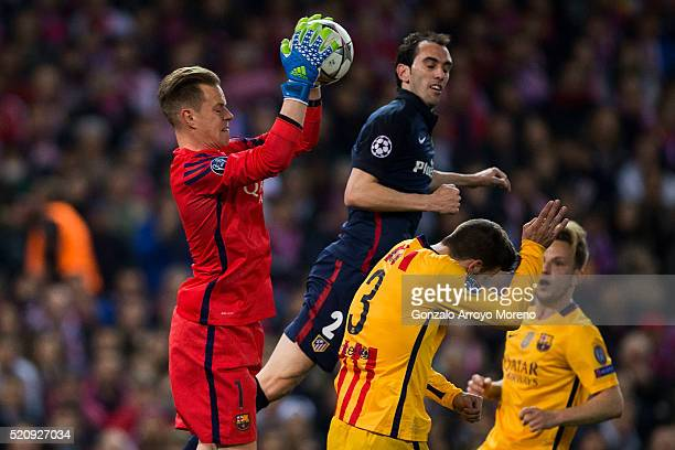 goalkeeper MarcAndre Ter Stegen of FC Barcelona stops the ball ahead Diego Godin of Atletico de Madrid during the UEFA Champions League quarter final...