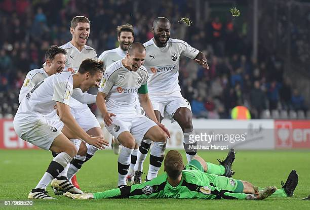Goalkeeper Marco Knaller of Sandhausen celebrates with his teammates after saving the last penalty during the DFB Cup match between SC Freiburg and...