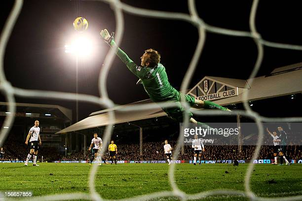 Goalkeeper Mark Schwartzer of Fulham dives in vain as Stephane Sessegnon of Sunderland scores his team's third goal during the Barclays Premier...