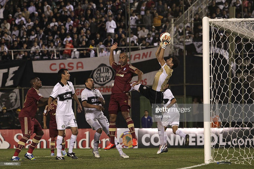 Goalkeeper <a gi-track='captionPersonalityLinkClicked' href=/galleries/search?phrase=Martin+Silva&family=editorial&specificpeople=4354248 ng-click='$event.stopPropagation()'>Martin Silva</a> (R) of Olimpia and Leandro Euzebio (C) of Fluminense fight for the ball during the match between Olimpia and Fluminense as part of the Copa Bridgestone Libertadores 2013, at Defensores del Chaco Stadium on May 29, 2013 in Asuncion, Paraguay.