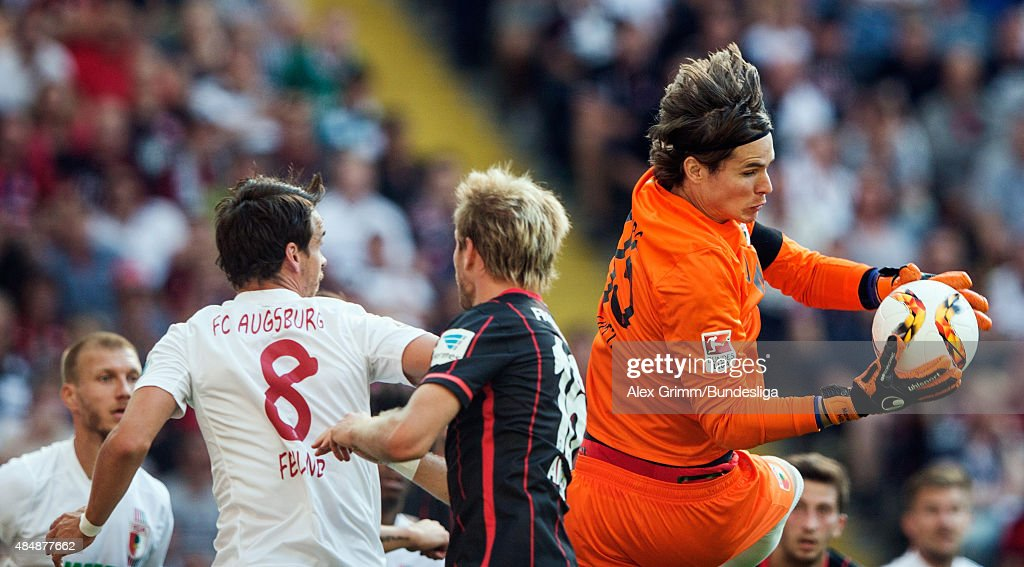 Goalkeeper <a gi-track='captionPersonalityLinkClicked' href=/galleries/search?phrase=Marwin+Hitz&family=editorial&specificpeople=5697209 ng-click='$event.stopPropagation()'>Marwin Hitz</a> of Augsburg makes a save ahead of <a gi-track='captionPersonalityLinkClicked' href=/galleries/search?phrase=Stefan+Aigner&family=editorial&specificpeople=764034 ng-click='$event.stopPropagation()'>Stefan Aigner</a> (C) of Frankfurt and <a gi-track='captionPersonalityLinkClicked' href=/galleries/search?phrase=Markus+Feulner&family=editorial&specificpeople=623655 ng-click='$event.stopPropagation()'>Markus Feulner</a> of Augsburg during the Bundesliga match between Eintracht Frankfurt and FC Augsburg at Commerzbank-Arena on August 22, 2015 in Frankfurt am Main, Germany.