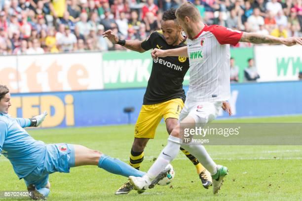 Goalkeeper Marwin Hitz of Augsburg PierreEmerick Aubameyang of Dortmund and Jeffrey Gouweleeuw of Augsburg battle for the ball during the Bundesliga...