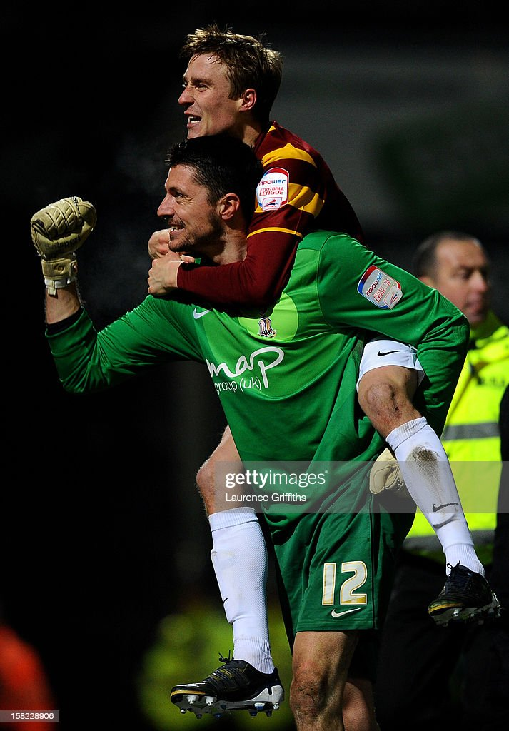 Goalkeeper Matt Duke of Bradford is congratulated by teammate Stephen Darby after saving penalty during the shootout to win the Capital One Cup quarter final match between Bradford City and Arsenal at the Coral Windows Stadium, Valley Parade on December 11, 2012 in Bradford, England.