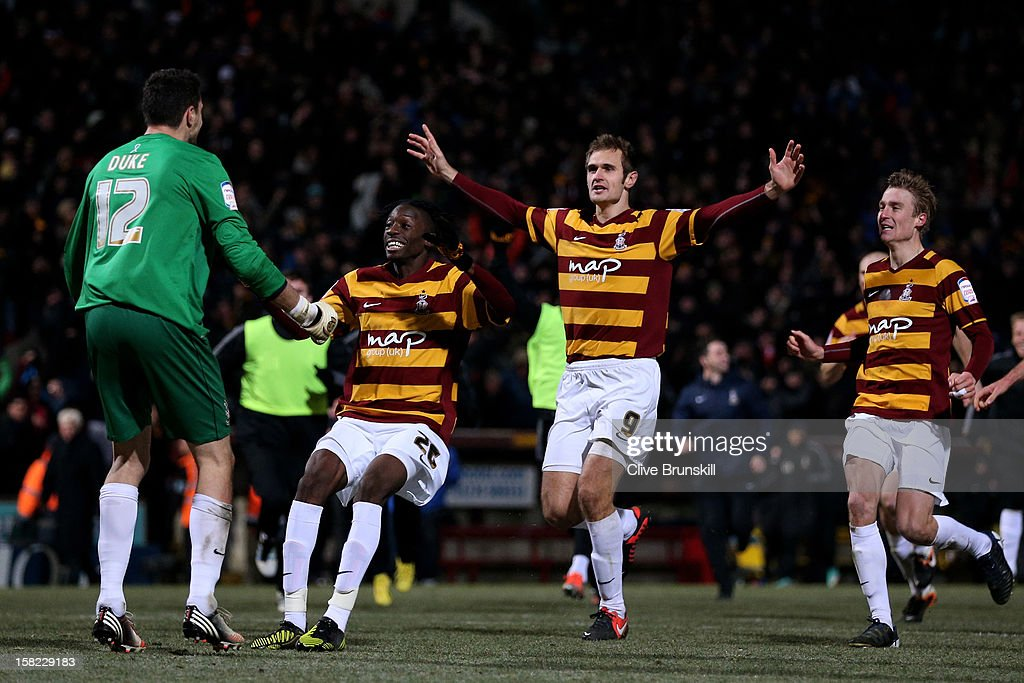 Goalkeeper Matt Duke of Bradford is congratulated by teammates after saving penalty during the shootout to win the Capital One Cup quarter final match between Bradford City and Arsenal at the Coral Windows Stadium, Valley Parade on December 11, 2012 in Bradford, England.