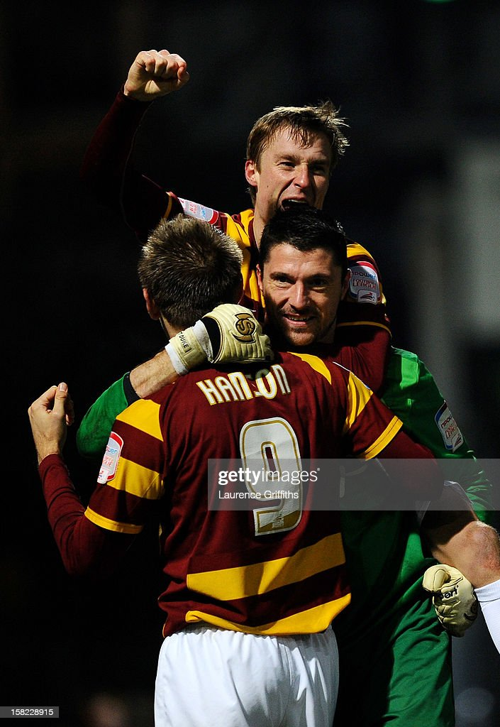 Goalkeeper Matt Duke of Bradford is congratulated by teammates Stephen Darby (T) and James Hanson #9 after saving penalty during the shootout to win the Capital One Cup quarter final match between Bradford City and Arsenal at the Coral Windows Stadium, Valley Parade on December 11, 2012 in Bradford, England.