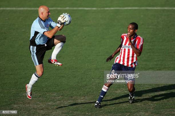 Goalkeeper Matt Reis of the New England Revolution makes the save as Atiba Harris of CD Chivas USA looks for a rebound in the second half during...