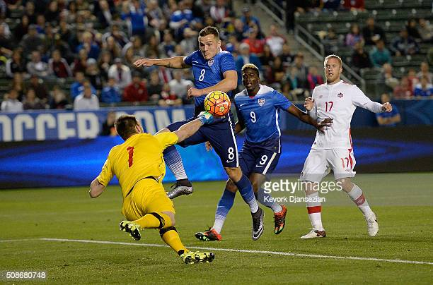 Goalkeeper Maxime Crepeau of Canada punches the ball for a save against Jordan Morris of the United States during the second half of their...