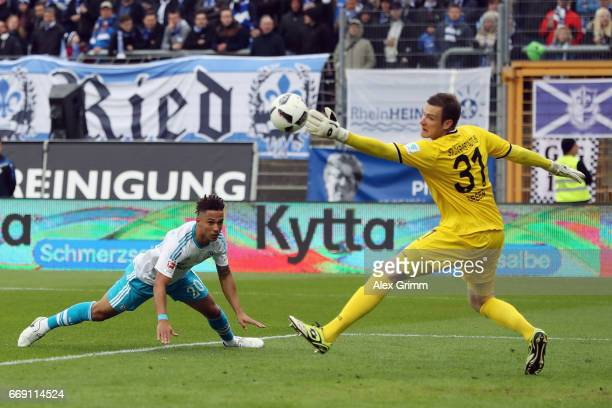 Goalkeeper Michael Esser of Darmstadt makes a save againt Dennis Aogo of Schalke during the Bundesliga match between SV Darmstadt 98 and FC Schalke...
