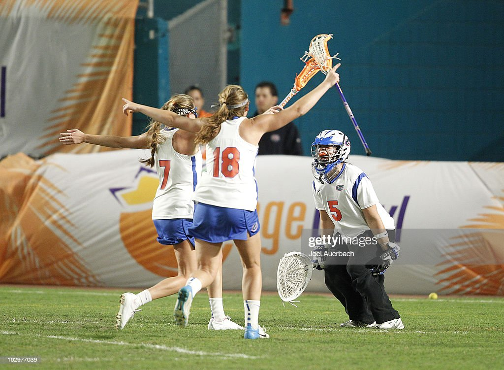 Goalkeeper Mikey Meagher #5 starts to celebrate the win with Jamie Reeg #7 and Sydney DuPre #18 of the Florida Gators against the Syracuse Orange during the 2013 Orange Bowl Lacrosse Classic on March 2, 2013 at SunLife Stadium in Miami Gardens, Florida.
