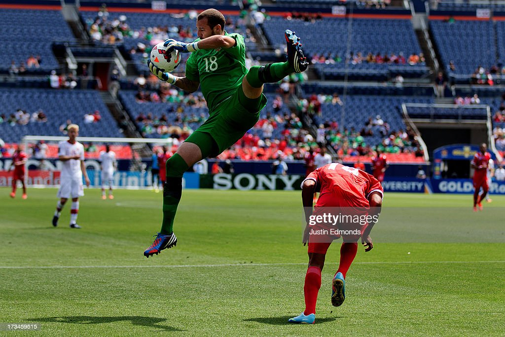 Goalkeeper Milan Borjan #18 of Canada jumps over Jairo Jimenez #18 of Panama to secure a ball in the air during the second half of a CONCACAF Gold Cup match at Sports Authority Field at Mile High on July 14, 2013 in Denver, Colorado. Canada and Panama played to a 0-0 draw.